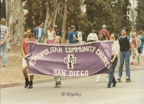 P104.142m.r.t Metropolitan Community Church at San Diego Pride Parade: Members of the Metropolitan Community Church marching behind purple MCC banner.