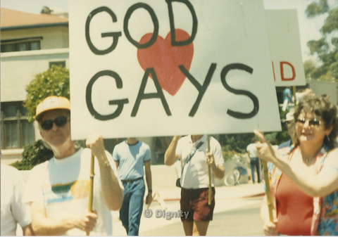 "P104.129m.r.t Dignity L.A. at San Diego Pride Parade: Shot of man and woman carrying ""GOD <3 GAYS"""