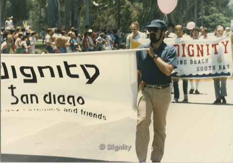 "P104.116m.r.t Dignity San Diego at San Diego Pride Parade: Man carrying ""Dignity San Diego: gay and lesbian catholics and friends"" banner standing in front of ""Dignity Long Beach South Bay"" banner."