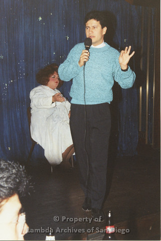P001.263m.r.t Through The Years Fundraiser: man in blue sweater holding microphone, drag queen in the background wearing a white dress and red wig