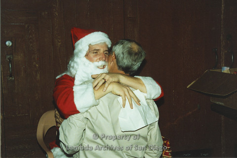 P001.290m.r.t X-mas: Santa hugging a man in a tan jacket