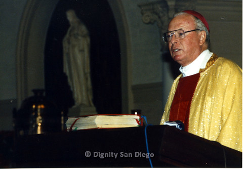 P103.060m.r.t Dignity San Diego: Religious leader with a red cap and golden robes speaking from podium