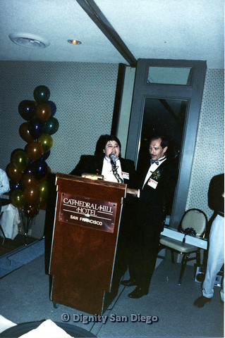 P103.124m.r.t Dignity Ninth Biennial Convention 1989: Two people in tuxedos, standing in front of a podium