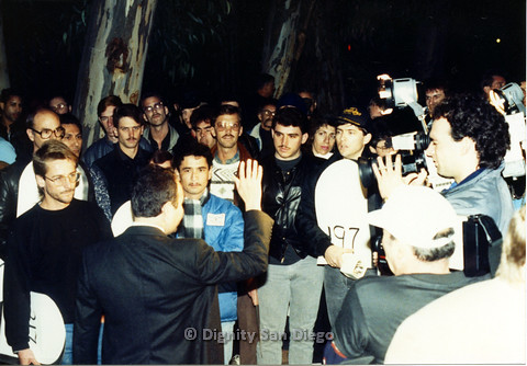 P103.087m.r.t Dignity San Diego: Large group of men holding numbers, with man at front in a suit raising hand and camera men recording.