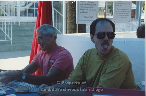 P001.112m.r.t 2 men sitting in booth, man on left is wearing a pink AIDS Foundation San Diego t-shirt