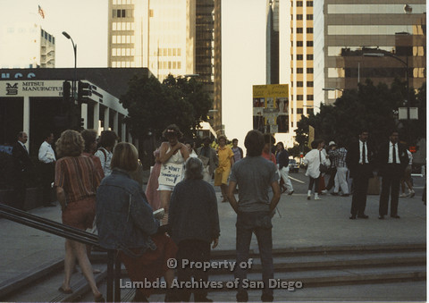 P024.125m.r.t Myth California Protest, San Diego, June 1986: candid shot of crowd, a Karen Merry with a sign around her neck (I Want a Scholarship Too)