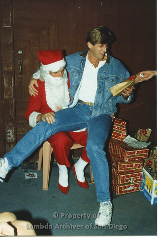 P001.278m.r.t X-mas: man in jean jacket sitting on Santa's lap being handed a present
