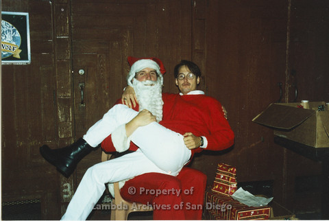 P001.297m.r.t X-mas: man in red sweater and white pants sitting on Santa's lap