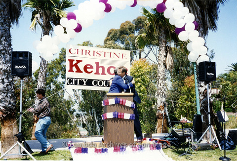 P151.011m.r.t Christine Kehoe hugging a man at the podium outside at a rally