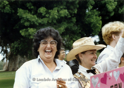 P024.445m.r.t 1990 San Diego Pride Parade: Joyce Mariel  smiling real big next to Diane Germain.
