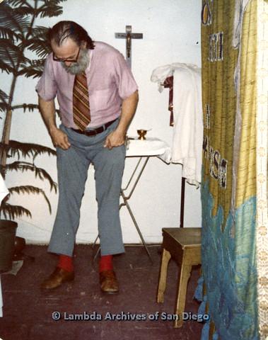 P110.047m.r.t Metropolitan Community Church: Joseph Gilbert bent over looking at socks with crucifix in backdrop.