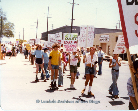 "P109.022m.r.t San Diego Pride Parade 1978: In the midst of parade with assorted signs and banners. Prominent ""Vote For Quality Education Vote Against Briggs"" sign."