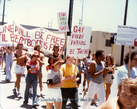P109.021m.r.t San Diego Pride Parade 1978: In the midst of parade with assorted signs and banners.