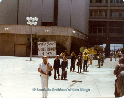 "P109.015m.r.t Civic Center Demo 1977: Picket line walking forward with prominent ""Anita Bryant is Archie Bunker in Drag"" sign."