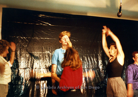 P024.181m.r.t Ellie Rapp off left while a woman fixes Judith McConnell's make-up and Kithy Gately top raises her arms up