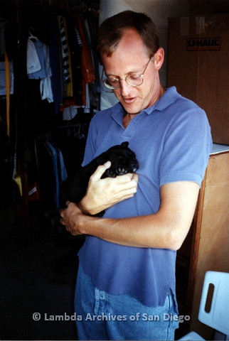 P151.016m.r.t Man in blue polo holding a black puppy