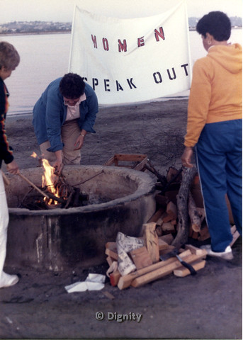 "P104.029m.r.t Dignity San Diego: Women feeind a bonfire with sign ""WOMEN SPEAK OUT"" in background"