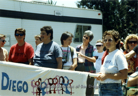 P024.470m.r.t 1990 San Diego Pride Parade: Group of women including Nancy Gordon in bluish gray shirt behind a banner with female symbols in the corner.