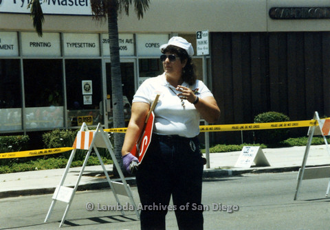 P024.448m.r.t 1990 San Diego Pride Parade: Wendy Sue Biegeleisen smoking a cigarette and holding a stop sign.