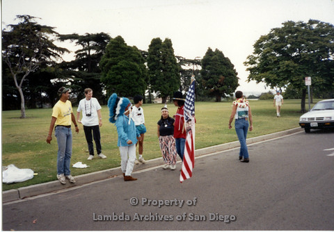 "P098.022m.r.t Nations of the 4 Directions marching at San Diego Pride Early 90s at Balboa Park, includes Ricky ""Cricket"" Kimball (far left), Jim Abrams (center, blue war bonnet), Giselle (center, black shirt), and Walter Twofeathers (right, carrying flag)"