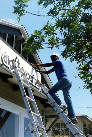 P103.166m.r.t San Diego Dignity Center: Man at top of ladder holding top of sign at front of Center