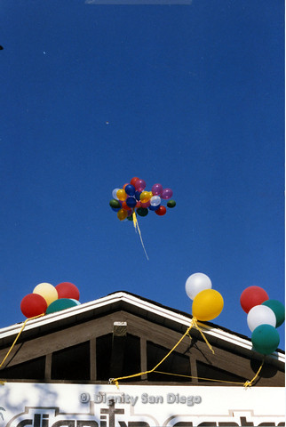 P103.183m.r.t San Diego Dignity Center: A group of balloons released into the air while others are attached to Center sign