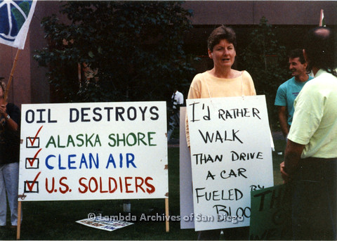 """P024.555m.r.t Judith McConnell holding sign that reads """" I'd RATHER WALK THAN DRIVE A CAR FUELED BY BLOOD"""""""