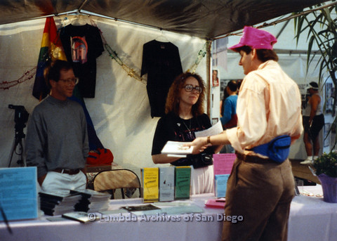P024.467m.r.t 1990 San Diego Pride festival: Man and Kate Johnson behind Lesbian and Gay Archives table with printed materials. Judith McConnell in pink hat stands in front.