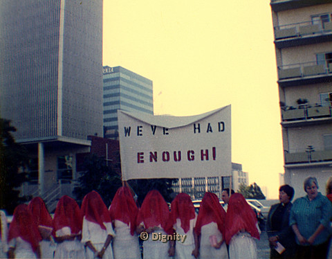 "P104.154m.r.t Group wearing white with red veils covering faces standing in front of sign that says ""WE'VE HAD ENOUGH."""