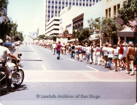 P109.030m.r.t San Diego Pride Parade 1978: View from rear of parade, police officer on motorcycle prominent on left side.