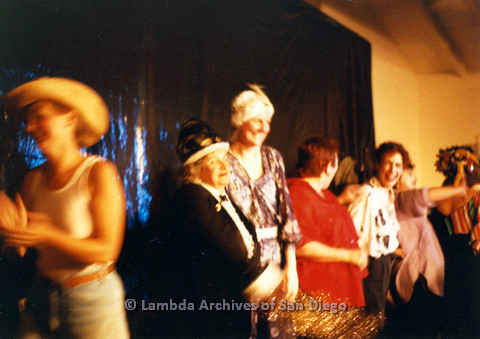 P024.189m.r.t Judith McConnell (center) laughing with other cast members, Diane Germain in cowboy hat (far left)