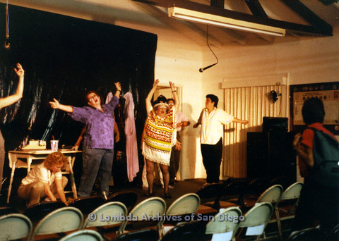P024.188m.r.t Ellie Rapp crouching while Muriel Fisher (in colorful poncho) and other casts perform
