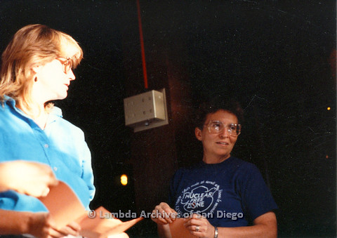 P024.179m.r.t Woman in blue collared shirt staring at another woman in dark blue