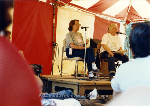 P024.252m.r.t Phyllis Lyons (left) and Del Martin (right) seated at the Day stage speaking in to microphones.