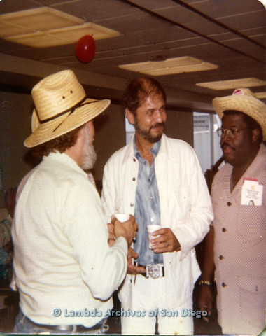 P110.046m.r.t Metropolitan Community Church: Joseph Gilbert conversing with group of men wearing straw hats.