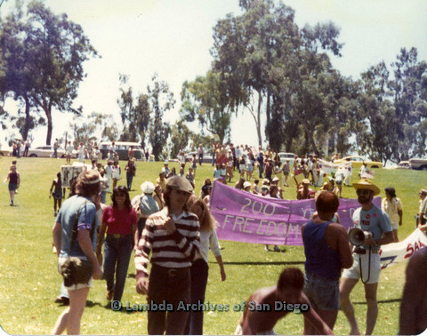 "P109.011m.r.t San Diego Pride Festival 1976: Gathering in Balboa Park. ""200 Years of Freedom"" banner in background."