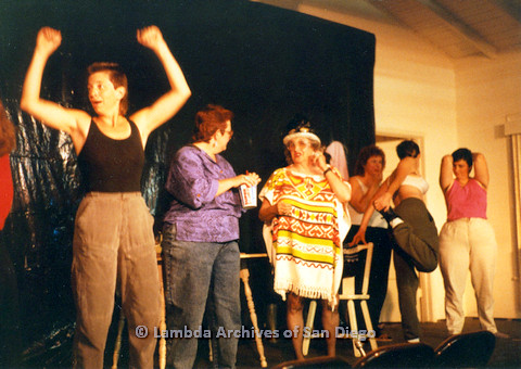 P024.184m.r.t Kithy Gately raising arms while Muriel Fisher in poncho talks to woman to her left