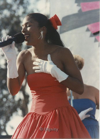 P104.150m.r.t San Diego Pride Festival 1989: Woman wearing red dress singing into microphone.