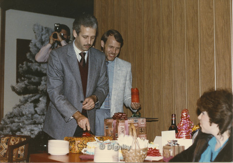 P104.082m.r.t Dignity San Diego: Bruce Neveu smiling behind man in grey suit cutting a cake