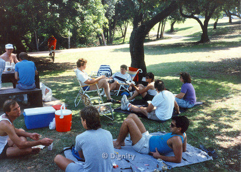 P104.051m.r.t Dignity Picnic 4th of July: Men and women sitting on the grass in the shade. (Judy Carton seated in rainbow chair, center)
