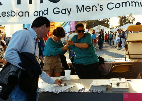 "P024.461m.r.t 1990 San Diego Pride festival: Two women in teal shirts behind the Center's table with printed materials. Man in blue button-up in front of table. Banner hangs above reads (partially), ""Lesbian and Gay Men's Comm…"""