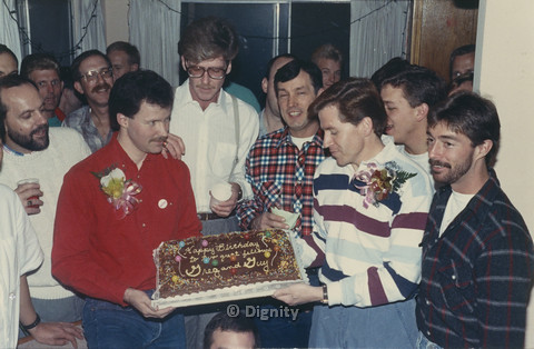P104.079m.r.t Dignity San Diego: Greg and Guy surrounded by friends while holding their birthday cake