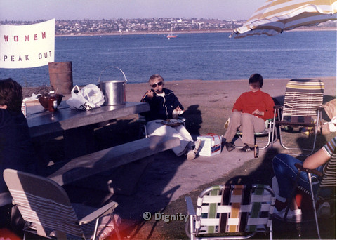"P104.027m.r.t Dignity San Diego: Women eating near the beach with sign ""WOMEN SPEAK OUT"" in background"