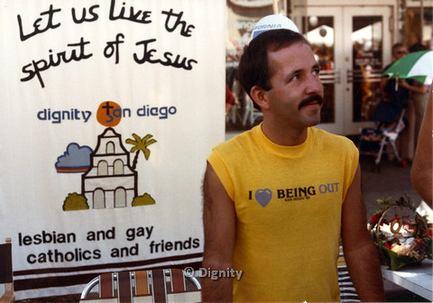 P104.012m.r.t Dignity San Diego: Man in yellow standing in front of Dignity San Diego sign