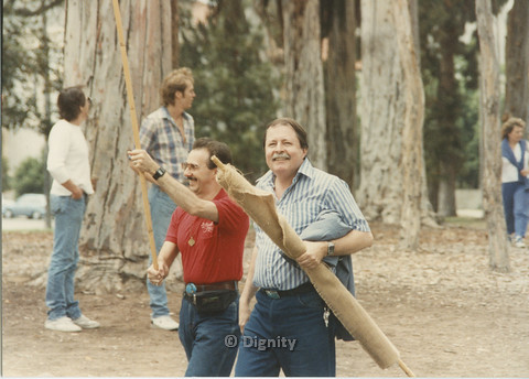 P104.145m.r.t San Diego Pride Festival: Two men walking forward while carrying long wooden poles.
