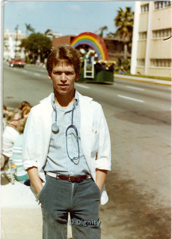 P104.178m.r.t San Diego Pride Parade: Man in lab coat and stethoscope standing with rainbow float in background.