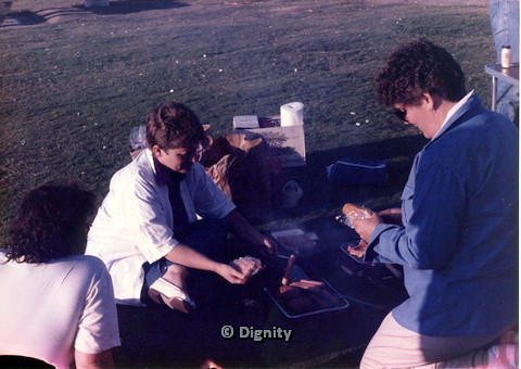 P104.025m.r.t Dignity San Diego: Women crowding around tray of hotdogs and burgers