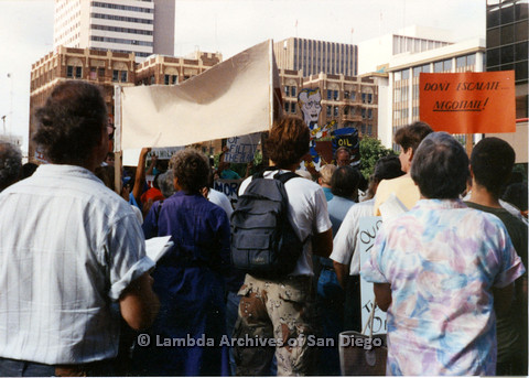 """P024.559m.r.t Group of people and an orange sign that reads """"DON'T ESCALATE… NEGOTIATE!"""""""