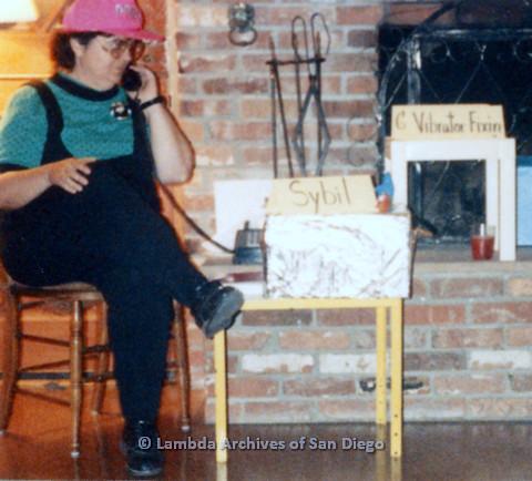P024.387m.r.t  A seated Michael Ann holding a telephone.