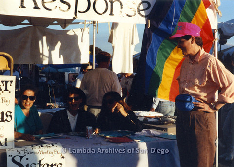 "P024.460m.r.t 1990 San Diego Pride festival: Three women sitting behind a Beautiful Lesbian Thespians (BLT) table with ""Sisters"" posters. Judith McConnell in pink hat stands in front."